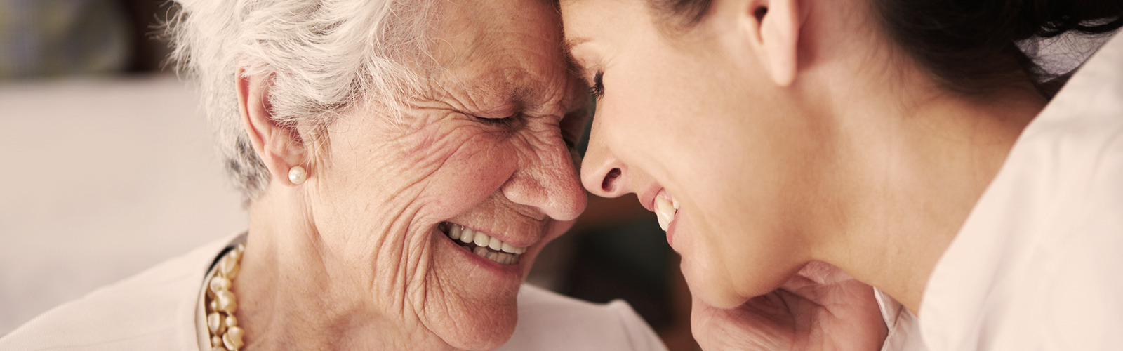 Elderly lady and younger woman laughing
