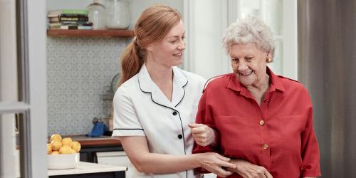 Sjuksköterska och äldre kvinna promenerar