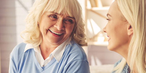 Older woman laughing with younger woman – ways to help your loved one with their incontinence