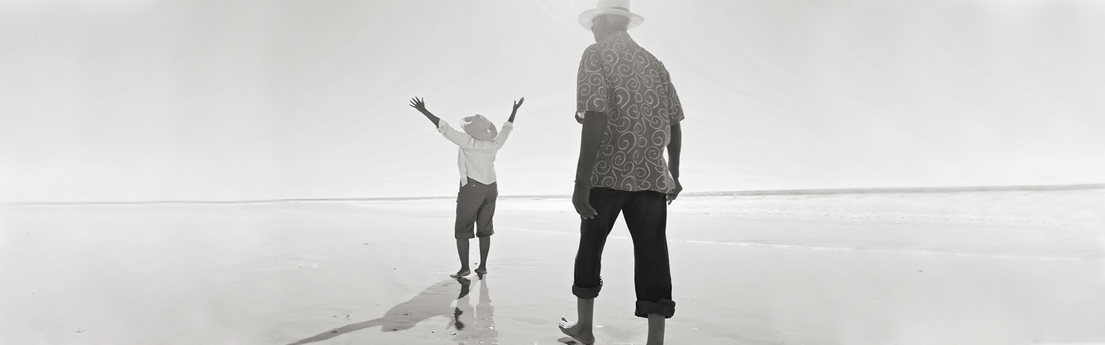 Young child walking on the beach with elderly man
