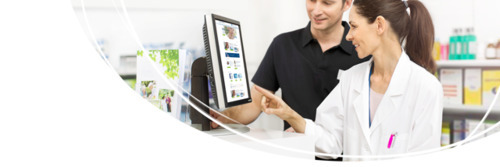Pharmacien aidant un client devant un ordinateur