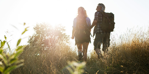 Mature man and woman hiking across a field in backlight