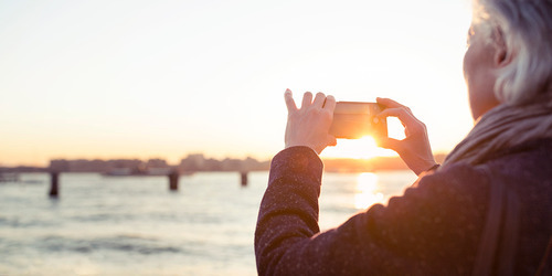 An elderly woman taking a photograph of the sunset