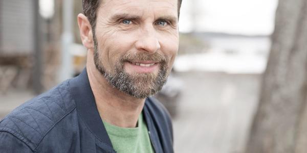 Homem sorridente de barba a usar
