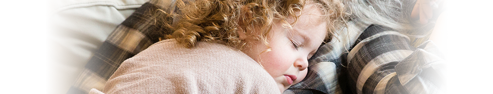 A little girl with curly hair asleep on an elderly woman