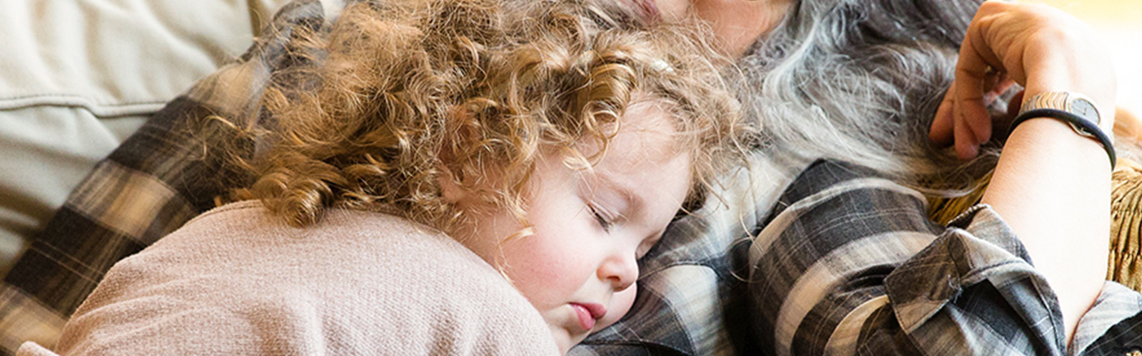 A young 3-year-old girl with curly strawberry blond hair is asleep on her mother's lap