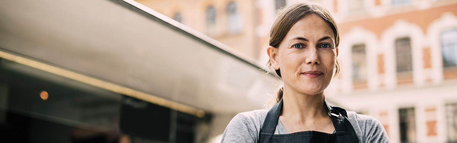 Front view of confident female chef standing by food truck in city