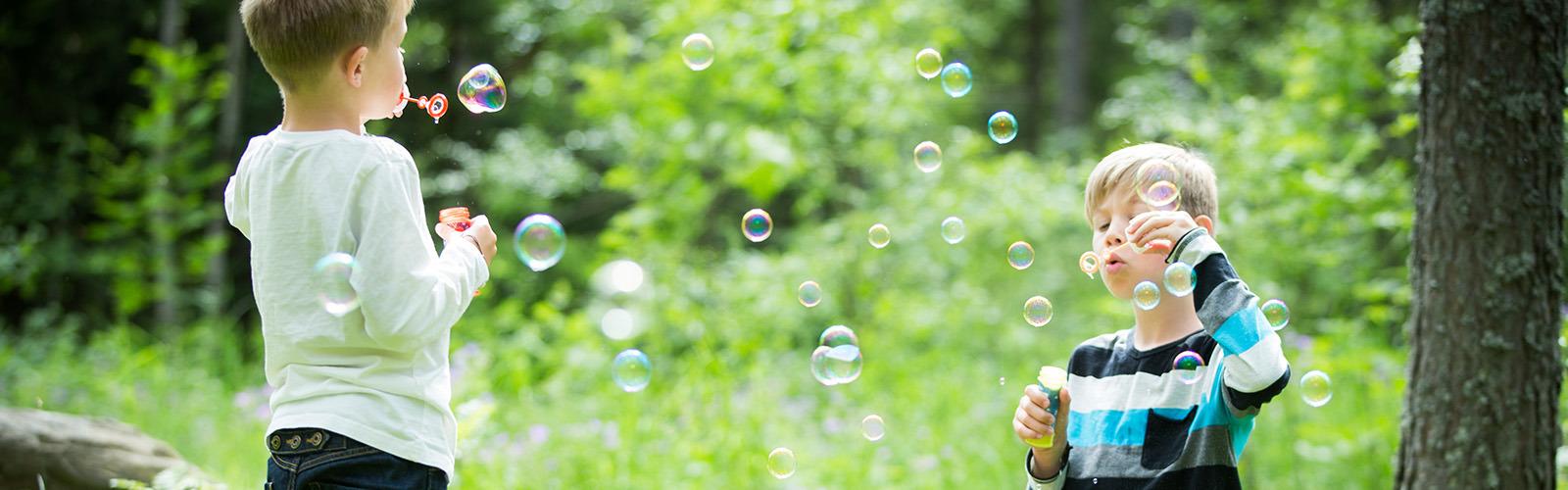 Brata, stara 4 in 7 let, veselo pihata balončke eden proti drugemu v gozdu, ki je obsijan s soncem.