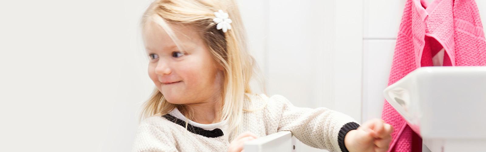 O fetiță neastâmpărată de 3 ani se întoarce spre cineva în timp ce deschide un sertar din baie, mândră că o poate face singură.