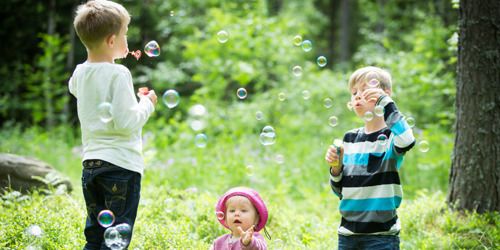 Two young brothers, 4 and 7-years-old, happily blowing bubbles towards each other in a sunny forest.
