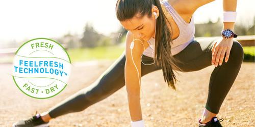 Pitkähiuksinen, poninhäntäinen nainen venyttelee jumpan jälkeen.