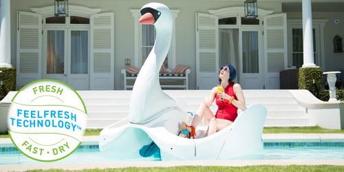 """Kvinde, der sidder i en svane i en swimmingpool ved siden af lights by TENA teksten """"light liners giver dig entør og frisk følelse""""."""