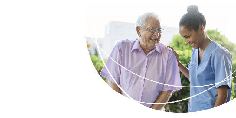 Image of Caregiver and Resident Walking in Garden - TENA Professional