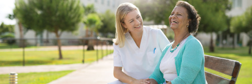 Image of Nurse and Resident on Park Bench  - Partnering With You To Make A Difference - TENA Professional