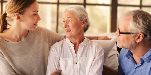 Pareja mayor sentada con mujer joven: cómo cuidar de tu ser querido sin sobrecargar tu cuerpo