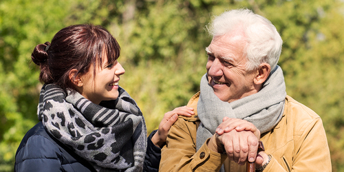 Hombre mayor sentado fuera con mujer joven: ayuda económica para cuidadores