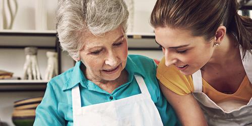 Idős nő süteményt süt egy fiatal nővel közösen – Az ápolással kapcsolatos leggyakoribb kérdések és a rájuk adott válaszok