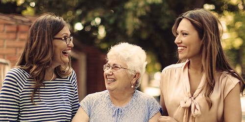 Femme âgée accompagnée de deux femmes plus jeunes dehors – comment le vieillissement affecte notre mobilité