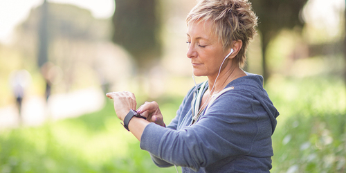 A female jogger with earplugs checks the time on her wrist watch