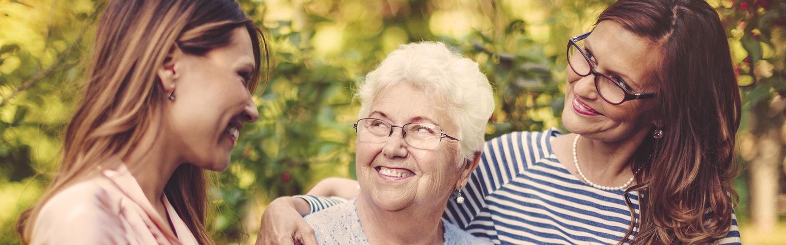 Idős nő két fiatal nő társaságában – Az ápolási feladatok felosztása