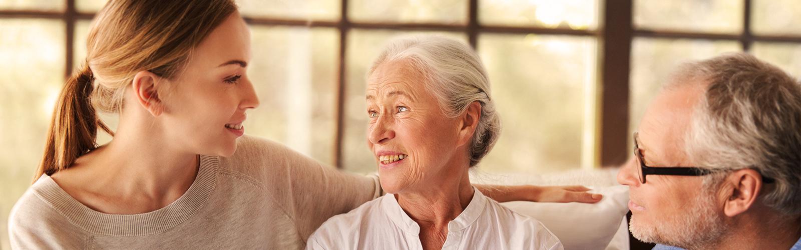 Starsza para siedząca z młodą kobietą – jak opiekować się bliskimi bez przeciążania się