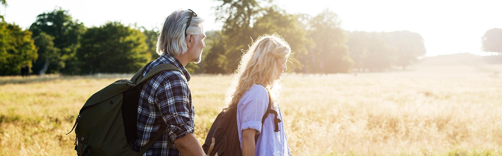 Мужчина и женщина с рюкзаками идут по солнечному полю