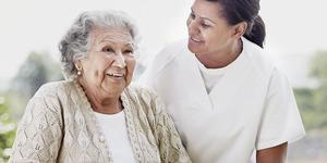 Asistentă medicală și femeie în vârstă bucurându-se una de compania celeilalte